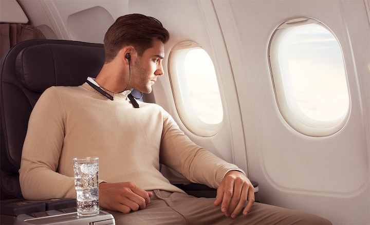 Lifestyle image of man listening to WI-1000XM2 headphones on an aircraft