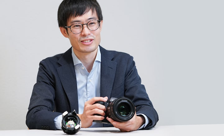 The Mechanical Design Lead holds the FE 50 mm F1.2 while delivering an explanation