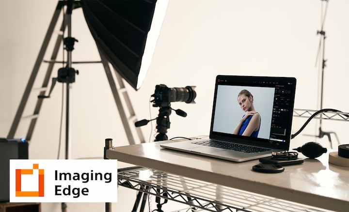 Image of studio illustrating Imaging Edge PC application, with camera on tripod and PC with camera image on screen